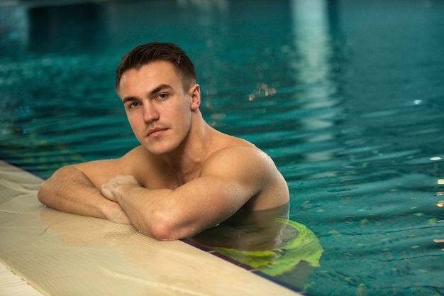 Handsome young man with athletic toned body resting by the swimming pool