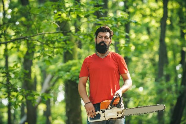 Красивый молодой человек с топором возле лесного дровосека концепции сельского хозяйства и лесоводства тема вырубки леса ...