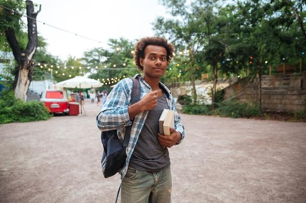 Красивый молодой человек с рюкзаком и книгами, стоя на открытом воздухе