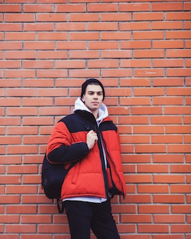 Handsome young man with backpack on red brick wall