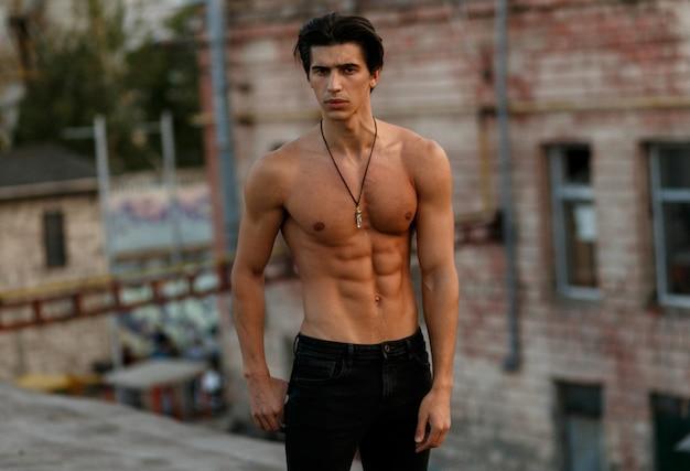 Красивый молодой человек с голым торсом в черных джинсах, глядя вниз, позирует с отношением на старой крыше снаружи. горизонтальный вид.