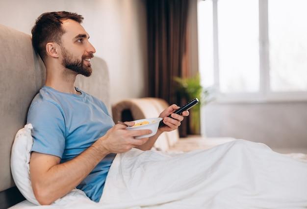 Красивый молодой человек с бородой завтракает в постели и смотрит телевизор
