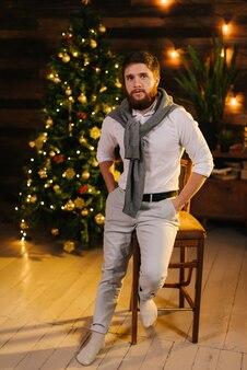 ひげを生やしたハンサムな若い男は、カメラを見て、お祝いの花輪とクリスマスツリーと壁を背景に笑顔です。