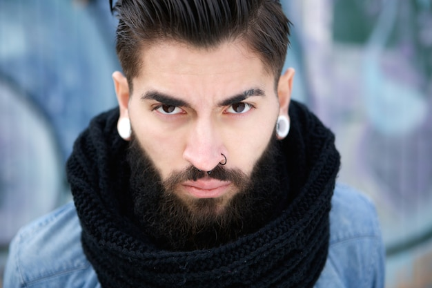 Handsome young man with beard and piercing