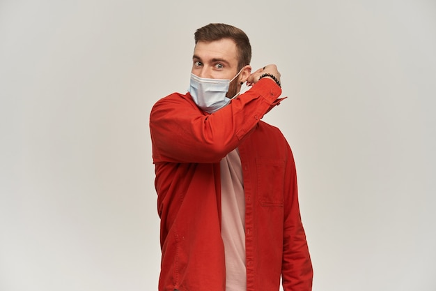 Handsome young man with beard in red shirt trying to take off or put on hygienic mask for preventing infection over white wall