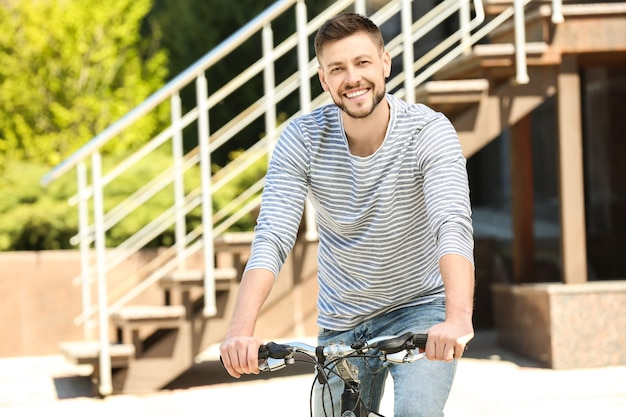 화창한 날 야외에서 자전거와 잘 생긴 젊은 남자