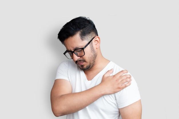 Красивый молодой человек в черных очках с болью в плече на белом фоне
