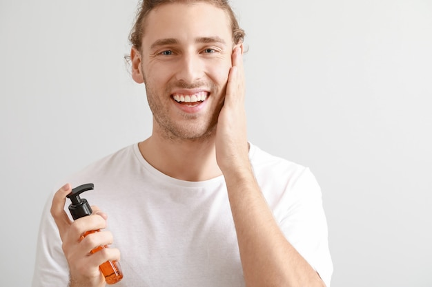 Красивый молодой человек с косметическим продуктом на светлом фоне