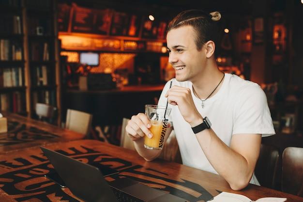 ノートパソコンとテーブルに座って、オレンジジュースとガラスを保持している軽いカジュアルシャツで創造的なヘアカットを持つハンサムな若い男