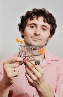 Handsome young man with curly hair with a small supermarket trolley on a light background