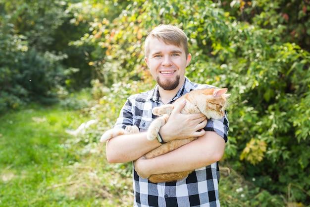 屋外でかわいい猫とハンサムな若い男