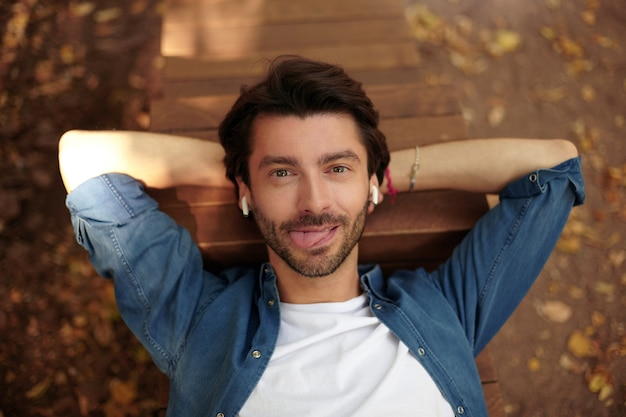 都市公園のベンチに横たわって、青いシャツと白いtシャツを着て見て楽しんでいる黒髪のハンサムな若い男
