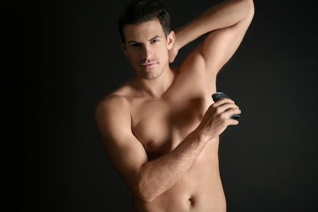 Красивый молодой человек с дезодорантом на темном фоне