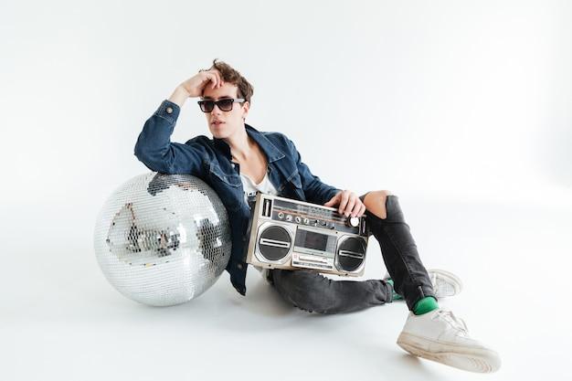 Красивый молодой человек с диско-шаром и бумбоксом