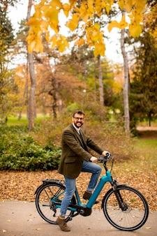 秋の公園で電動自転車を持つハンサムな若い男