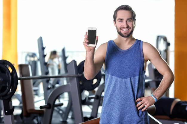 Красивый молодой человек с фитнес-трекером и мобильным телефоном в тренажерном зале