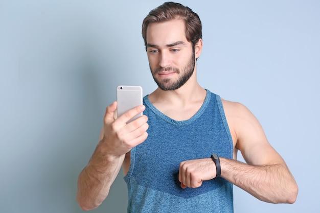 Красивый молодой человек с фитнес-трекером и мобильным телефоном на цветном фоне