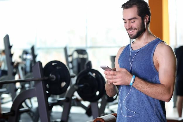 Красивый молодой человек с фитнес-трекером, слушать музыку в тренажерном зале