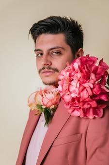 ピンクのスーツを着て、首に花を持つハンサムな若い男
