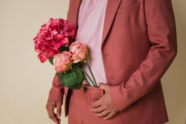 ピンクのスーツを着て、彼のズボンの中に花を持つハンサムな若い男