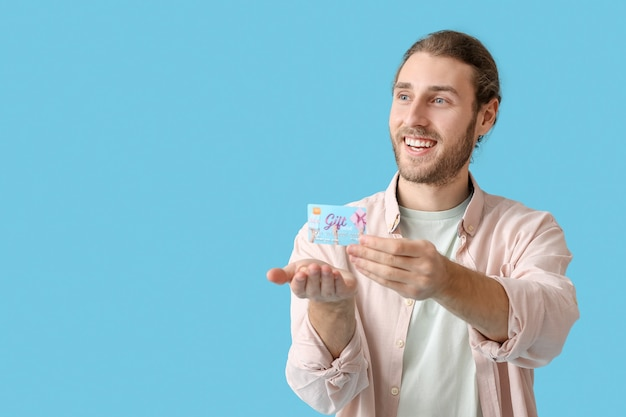 Handsome young man with gift card on color surface