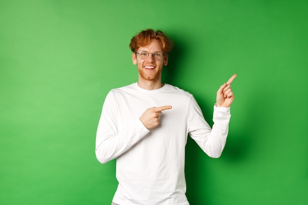 Handsome young man with ginger hair and glasses, pointing fingers right at copy space and smiling, standing over green background.