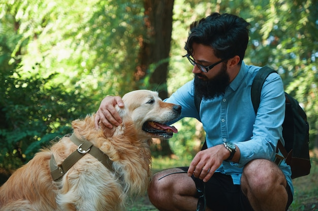 Handsome young man with golden retriver outdoors