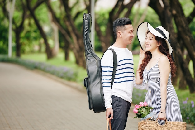 Handsome young man with guitar looking at happy laughing pretty girlfriend when they are standing in park