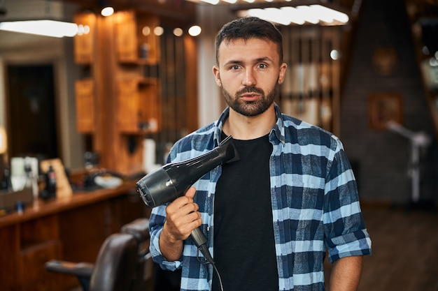 Handsome young man with hair dryer standing in barbershop