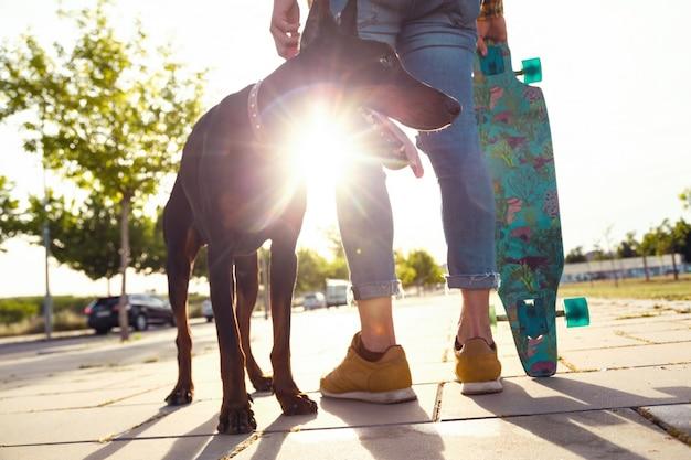 公園でスケートボードをしている彼の犬のハンサムな若い男。 Premium写真