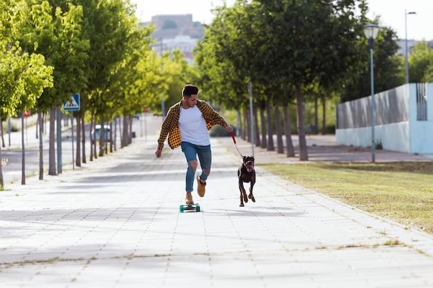公園でスケートボードをしている彼の犬のハンサムな若い男。