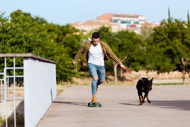 Handsome young man with his dog skateboarding in the park.