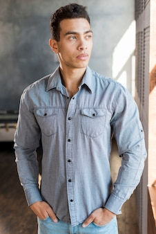 Handsome young man with his hands in pocket looking away