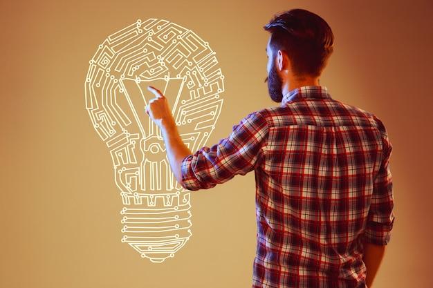 抽象的なランプの背景にアイデア電球を持つハンサムな若い男。コンセプトの新しいアイデア