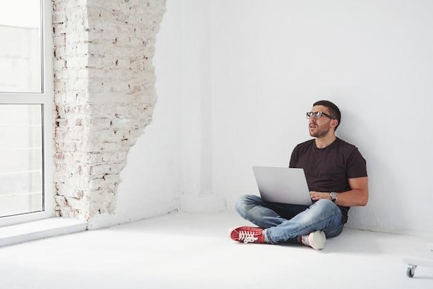 ノートパソコンでハンサムな若い男と白の彼の時刻表をチェック