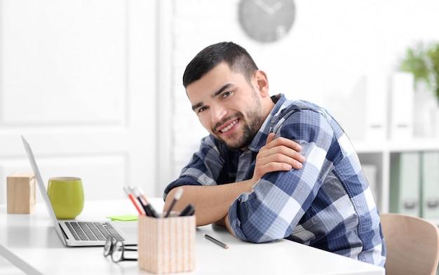 テーブルでラップトップを持つハンサムな若い男