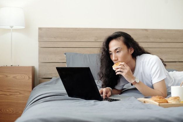Handsome young man with long hair lying on bed eating fresh bun and watching webinar or tutorial on ...