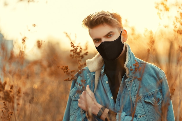Handsome young man with medical protective mask in fashion denim clothes look with sweater looking at the camera outdoors at sunset