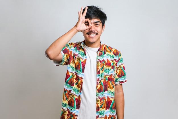手と指でokサインをやってポジティブに笑って白い背景の上にカジュアルなtシャツを着ている口ひげを持つハンサムな若い男。成功した表現。