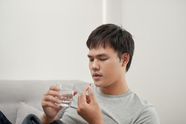 自宅で錠剤と水の入ったグラスを持つハンサムな若い男