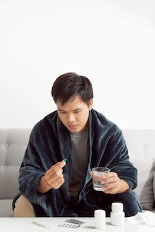 Handsome young man with pill and glass of water at home