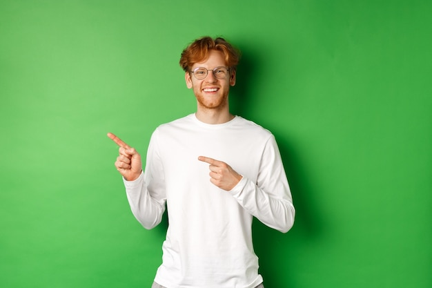 빨간 머리와 수염 웃 고, 로고에서 왼쪽 손가락을 가리키는 잘 생긴 젊은 남자, 녹색 배경 위에 서 광고를 게재.