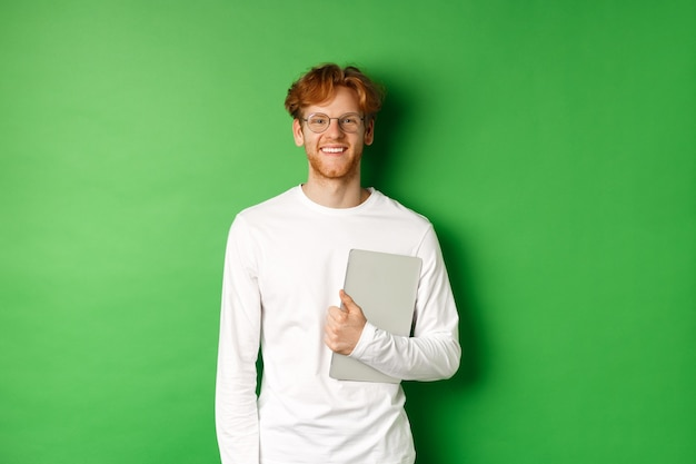 Handsome young man with red hair, wearing glasses and long-sleeve t-shirt, holding laptop on green background.
