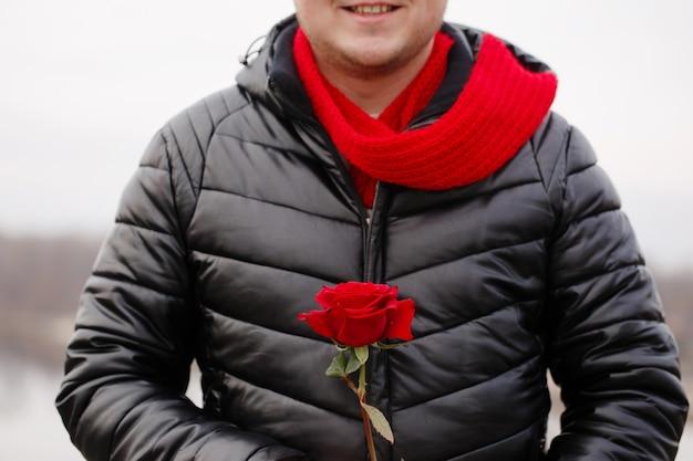 雪の降る天気の屋外で手に赤いバラを持つハンサムな若い男