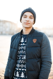 Handsome young man with a sweet smile in a vintage stylish hat in a christmas knitted sweater in a fashionable jacket stands in the city. stylish happy charming guy for a walk.