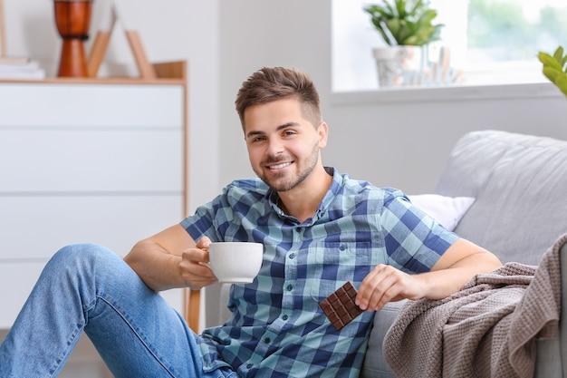 家でおいしいチョコレートとお茶のカップを持つハンサムな若い男
