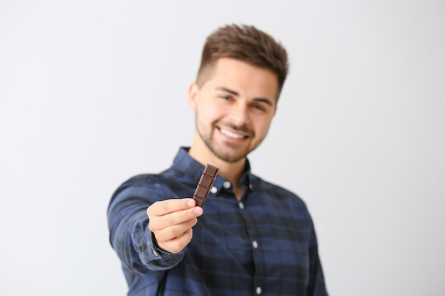 Handsome young man with tasty chocolate on light background