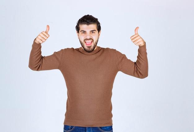 Красивый молодой человек с большими пальцами руки вверх и улыбается.