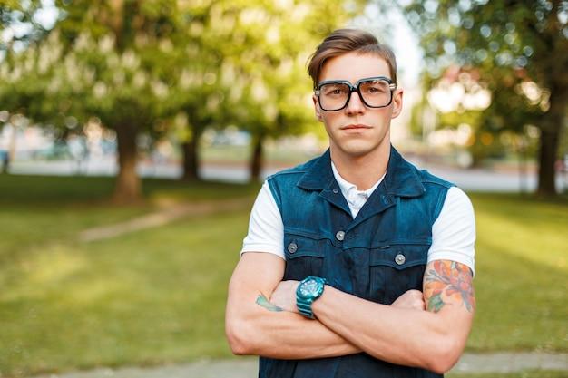 公園で夏の日にヴィンテージのメガネとジーンズのチョッキを持つハンサムな若い男