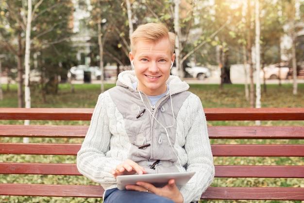 흰색 헤드폰을 끼고 있는 잘생긴 청년은 가을에 도시의 벤치에 앉아 있다